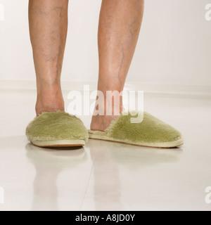 Caucasian senior female feet wearing green bedroom slippers - Stock Photo