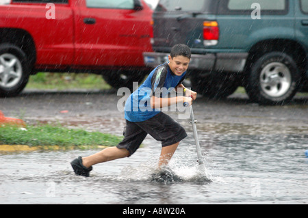 Boy riding scooter skateboard through flooded puddle of water - Stock Photo