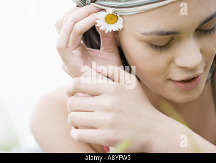 Young woman putting flower behind ear - Stock Photo