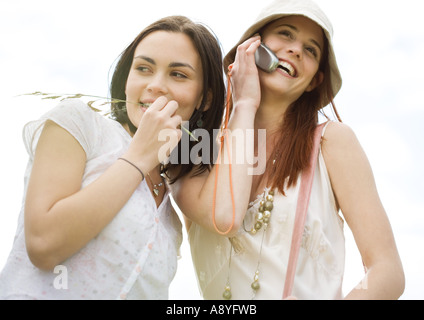 Two young woman outdoors, one using cell phone - Stock Photo