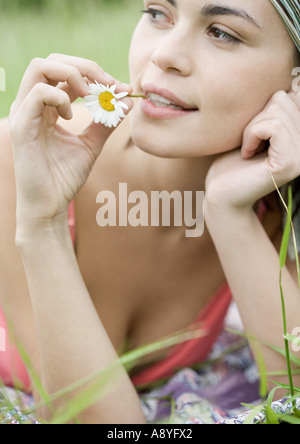 Young woman with flower stem in mouth - Stock Photo