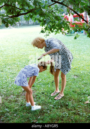 mother doing hairstyle for daughter in park MR8417 7A - Stock Photo