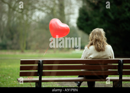 A young woman sits alone on a park bench - Stock Photo