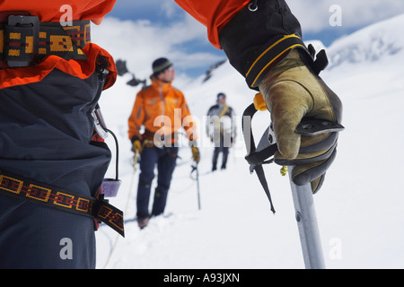 Hikers using walking sticks in snowy mountains, mid section on front man - Stock Photo