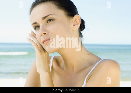 Woman touching face with back of hand, sea in background, head and shoulders - Stock Photo