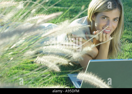 Young woman lying in field with laptop - Stockfoto