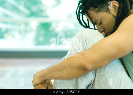 Man sitting with knees up and head down - Stock Photo