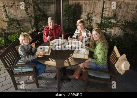 Portrait of a family eating sushi together - Stock Photo