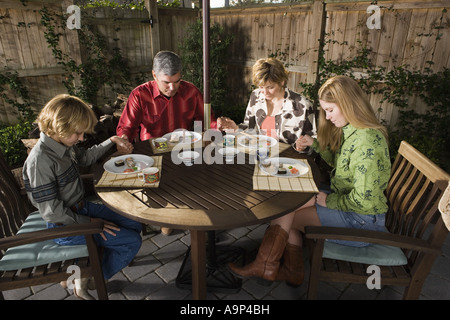 Portrait of a family saying grace before eating sushi together - Stock Photo