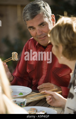Mature couple eating sushi - Stock Photo