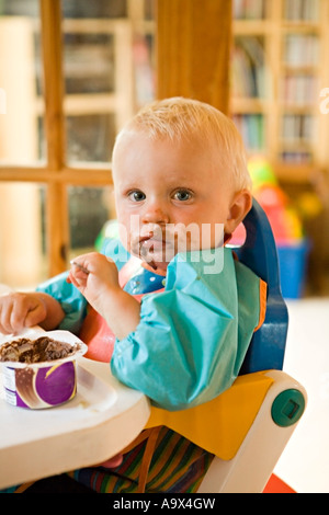 Beautiful young baby eating chocolate pudding in a baby chair looking at the camera - Stock Photo