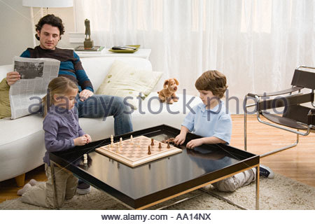 Brother and sister playing chess - Stock Photo