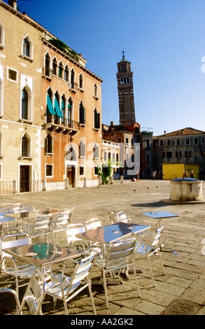 Italy, Venice, A church tower Campo San Stefano Saint Steven square Cannaregio, tables and chairs in town square - Stock Photo