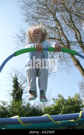 young girl jumping on small trampoline - Stockfoto