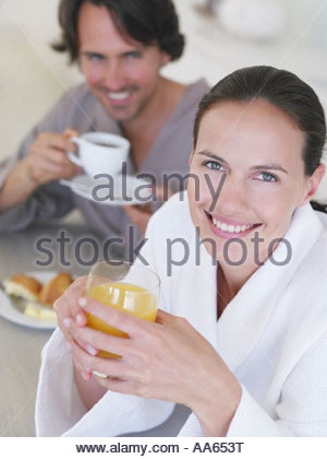 Woman in robe with orange juice and man in background - Stock Photo