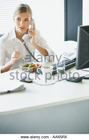 Businesswoman eating salad and talking on telephone at desk - Stock Photo