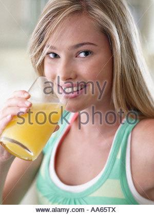 Closeup of teenage girl drinking orange juice smiling - Stock Photo