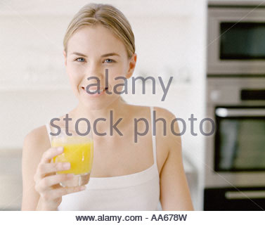 Woman with glass of orange juice smiling - Stock Photo