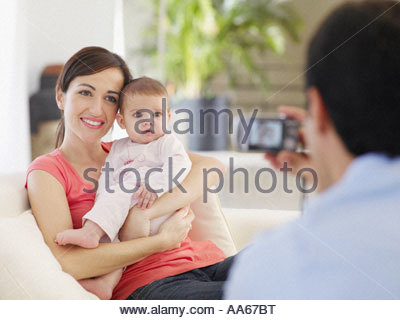 Mother and baby daughter posing while father takes a picture - Stock Photo