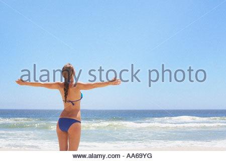 Rear view of woman in bikini stretching - Stock Photo