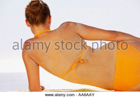 Rear view of woman in bikini with sand on back - Stock Photo