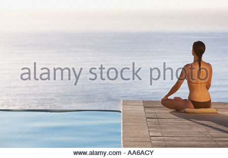 Woman sitting on infinity pool deck doing yoga rear view - Stock Photo