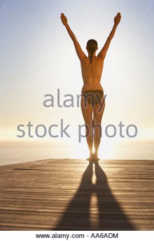 Woman on pool deck doing yoga - Stock Photo