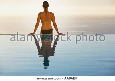 Woman sitting on edge of infinity pool in bikini - Stock Photo