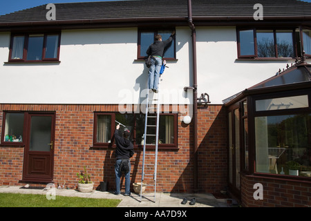 NORTH WALES April Two young man up a ladder cleaning the first floor windows standing on ground cleaning kitchen - Stock Photo