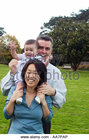 Mother, father and baby playing - Stock Photo