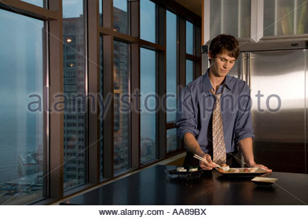 Young adult man eating sushi in kitchen - Stockfoto