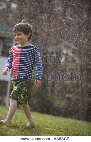 A young boy standing in a sprinkler Stock Photo - Alamy