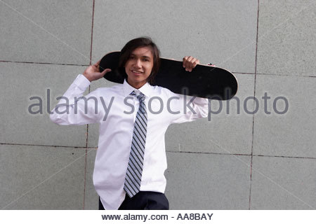 Young adult man holding skateboard - Stock Photo