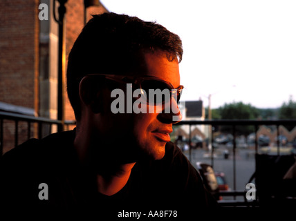 young man at sunset wearing sunglasses in Canada - Stock Photo