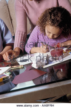 Mother watching African daughter drawing - Stock Photo