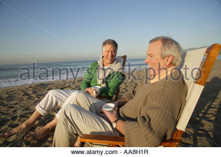 Mature men relaxing on beach - Stock Photo