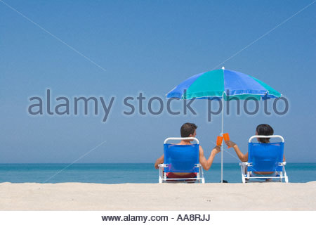 Young couple toasting in lawn chairs on beach - Stock Photo