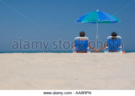 Young couple holding hands in lawn chairs on beach - Stock Photo