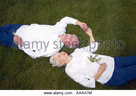 Senior couple laying in grass  - Stock Photo