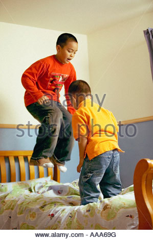 African brothers jumping on the bed - Stock Photo