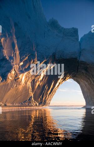Greenland Ilulissat Setting midnight sun lights massive arched iceberg from Ilulissat Kangerlua Glacier Jakobshavn - Stock Photo
