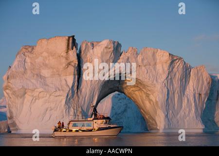 Greenland Ilulissat Tourists boat sails past massive arched iceberg from Ilulissat Kangerlua Glacier Jakobshavn - Stock Photo