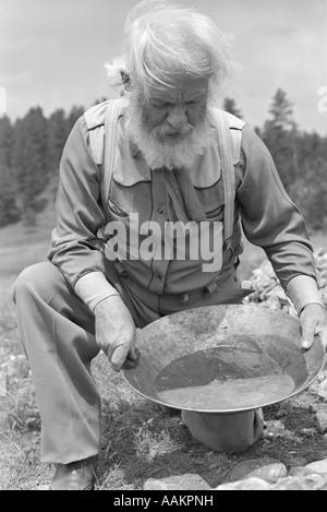 1940s 1950s ELDERLY BEARDED MAN PROSPECTOR PANNING FOR GOLD - Stock Photo