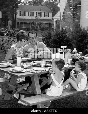 1960s SUBURBAN FAMILY OF FOUR AT PICNIC TABLE IN BACKYARD EATING - Stock Photo