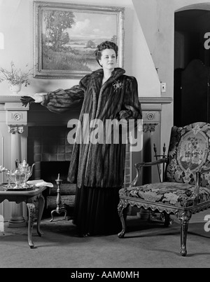 1940s WOMAN IN FORMAL LIVING ROOM STANDING IN FRONT OF FIREPLACE WEARING FULL-LENGTH FUR LOOKING AT CAMERA - Stock Photo