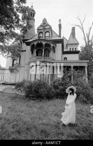 WOMAN IN VICTORIAN COSTUME STANDING ON FRONT LAWN OF LARGE VICTORIAN HOME - Stock Photo
