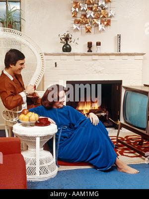 1970s COUPLE IN LIVING ROOM SITTING IN FRONT OF TELEVISION AND BESIDE A FIRE - Stockfoto
