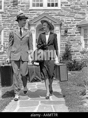 1930s 1940s SMILING COUPLE LEAVING HOME CARRYING LUGGAGE - Stock Photo
