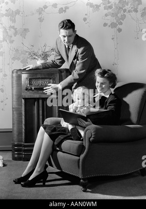 1930s 1940s FAMILY LISTENING TO RADIO WHILE MOTHER READS BOOK TO LITTLE GIRL SEATED IN HER LAP IN ARMCHAIR - Stock Photo