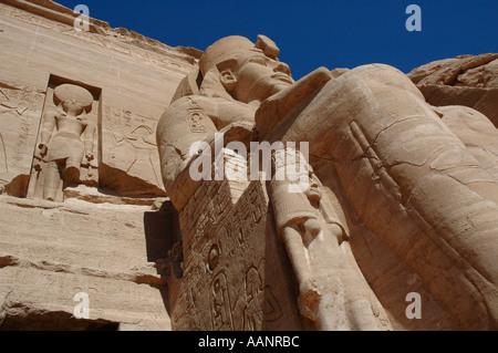 Great Temple of Rameses II Abu Simbel Egypt Closeup of single statue of Rameses II and hawk headed sun God Ra - Stock Photo